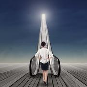 Businesswoman on escalator to get her aim Stock Photos