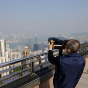 Tourist looking in Telescope - stock photo
