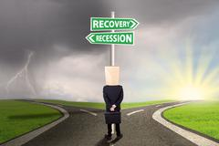 Stock Photo of Entrepreneur look at signboard with recovery recession words