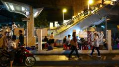 Street eatery against BTS station escalator, night time, people walking Stock Footage