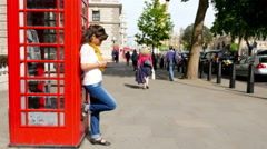 Woman using smart phone while leaning on a red phone booth in London Stock Footage