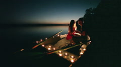 Young love romance on boat with candles at night on the lake Stock Footage