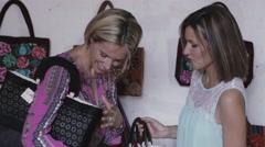 Women trying on handbags Stock Footage