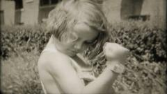 2414 - little girl flexes her muscles for the camera - vintage film home movie Stock Footage