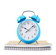 Blue alarm clock over the notebook Stock Photos