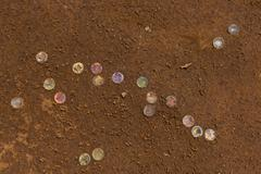 Discarded soda caps in ground, Tanzania, Africa - stock photo