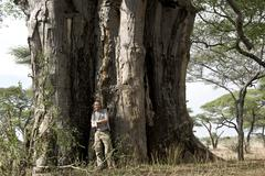 Portrait of man standing in front of a baobab, Tanzania, Africa - stock photo