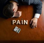 Word Pain and devastated man composition - stock photo