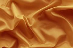Closeup of lines in orange silk fabric - stock photo