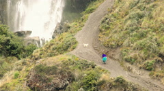 Quechua peasant woman with dog on unpaved countryside road Stock Footage
