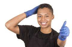 Closeup hispanic young man wearing blue cleaning gloves facing camera with right Stock Photos