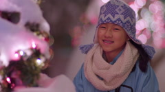 Girl Smiles With Holiday Spirit, Standing Next To Snow Covered Christmas Tree - stock footage
