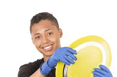 Closeup hispanic young man wearing blue cleaning gloves holding up yellow plate - stock photo