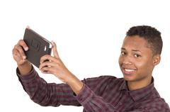 Young hispanic man with casual clothing holding up white tablet as in taking - stock photo