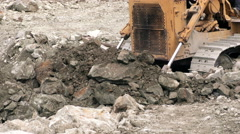 Bulldozer moving large quantity of loose rocks - stock footage