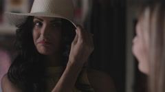 Women trying on hat - stock footage