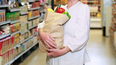 Senior woman with bag of veg in grocery store Stock Footage