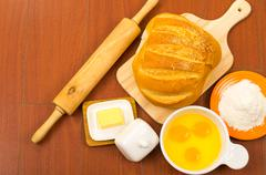 Loaf of bread, cheese, cracked eggs in a bowl and flour displayed on wooden Stock Photos