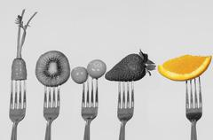 Five forks vertical position showing black and white carrot, kiwi, gooseberry - stock photo