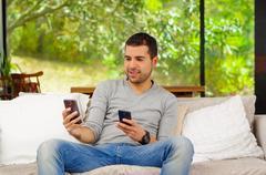 Hispanic man wearing denim jeans and grey sweater sitting on sofa comfortably Stock Photos