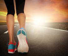 Runner feet running on road - stock photo