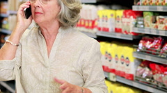 Senior woman shopping in grocery store Stock Footage