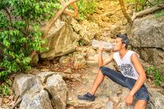 Man hiker drinking water in roasting day. - stock photo