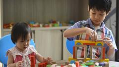 Children playing with blocks on table Stock Footage