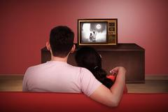 Young asian couple watching retro tv Stock Photos