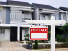 House for sale board with house background Stock Photos
