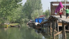 Woman and child walk across small bridge at Dal Lake,Srinagar,Kashmir,India Stock Footage