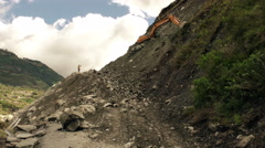 Large tracked backhoe cleaning landslide affected road Stock Footage