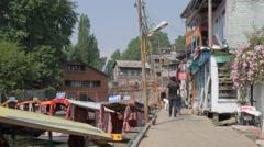 People walk along Dal Lake with docked shikara boats,Srinagar,Kashmir,India - stock footage
