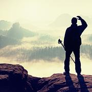 Silhouette of tourist with poles in hand. Hiker stand on rocky view point abo - stock photo