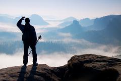 Stock Photo of Silhouette of tourist with poles in hand. Hiker stand on rocky view point abo