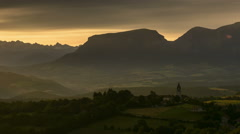Church steeple hit by dawn sunrays time lapse Ecrins National park  Stock Footage