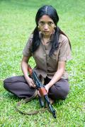 Asian woman with a machine gun sits on grass - stock photo