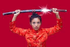 Asian woman holding a samurai sword over his head - stock photo