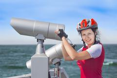 Girl in cyclist uniform and big spyglass - stock photo