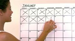 Woman marking off dates on calendar - stock footage