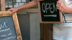 Cafe owner showing open sign - stock footage