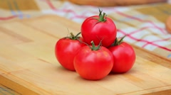 beautiful tomatoes lie on a culinary board - stock footage