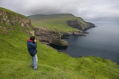 Photographer taking pictures on Mykines, Faroe Islands - stock photo
