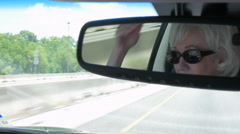 Wider view from rear view mirror of woman driving on an interstate highway Stock Footage