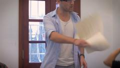 A casual boss loses control of a meeting while his coworkers throw paper at him Stock Footage