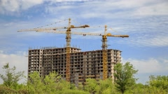 Construction of concrete buildings on background moving clouds - stock footage