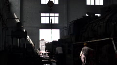 Worker working in steam train repairing factory Stock Footage