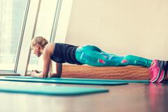 Blonde female doing plank static exercise in gym - stock photo