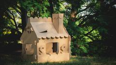 Toy house made of corrugated cardboard in the city park - stock photo