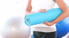 Smiling athletic woman carrying yoga mat Stock Footage
